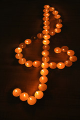 Burning candles as treble clef on dark background