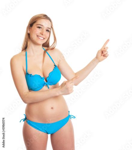 Frau im blauen Bikini zeigt zur Seite
