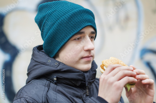 Teenager starting to eat burgers at outdoor