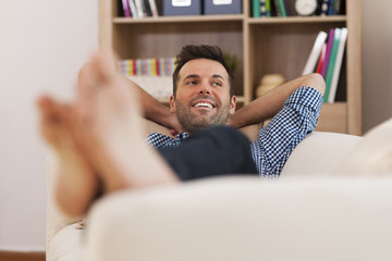 Happy man relaxing on couch