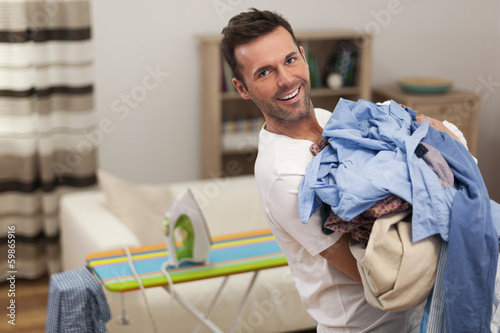Portrait of smiling man with stack of shirts for ironing