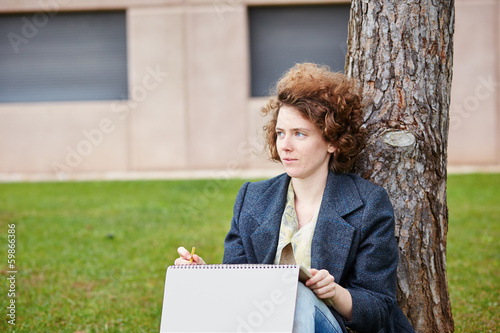 Female redhead art student drawing outdoors