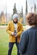 Young bearded hipster taking photo to redhead girl with TLR came