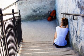 Frau sitzt auf einer Treppe
