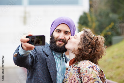 Couple taking a photograph of themselves kissing with a smartpho