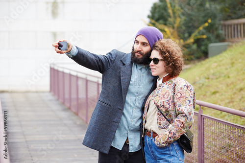 Couple taking a photograph of themselves with a smartphone