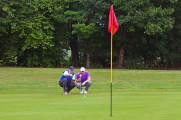Golfer and caddy putting green.