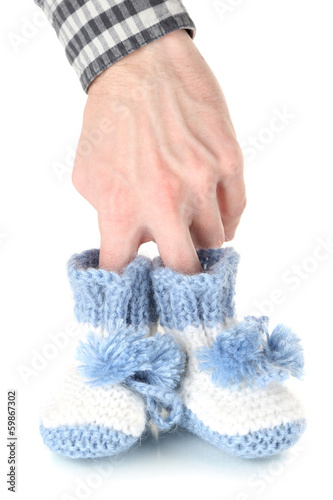 Hand with crocheted booties for baby, isolated on white