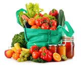 Green shopping bag with variety of fresh organic vegetables isol