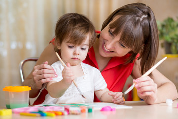 mother and kid girl paint together at home