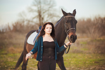 Young woman with a horse on nature