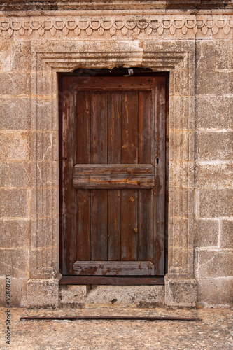ancient wooden door in stone wall