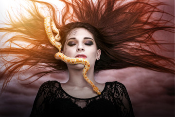 Woman lying on the floor with eyes closed, face the snake