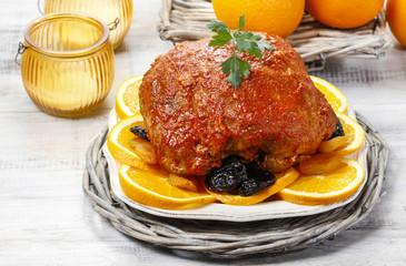 Pork served on oranges and plums. Festive dinner