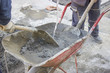 workers mixing the cement by hand in wheelbarrow 3