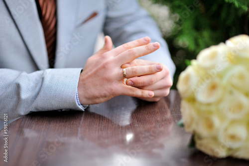 Groom is sitting at the table and twists the ring on her finger