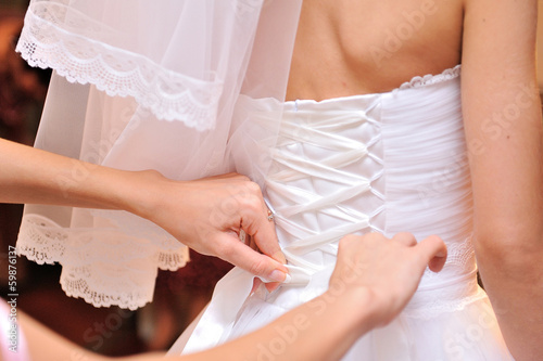 bridesmaid tying bow on wedding dress