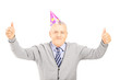 Happy mature gentleman with party hat giving thumbs up