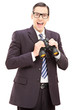 Smiling young businessman holding binoculars