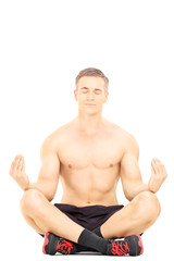 Handsome shirtless man meditating seated on a floor