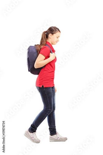 Full length portrait of a sad schoolgirl with a bag walking