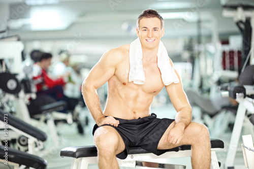 Muscular young guy sitting on a bench in a gym