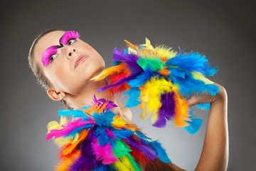 Beautiful young female model with bold make-up and feathers