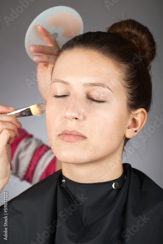 Make-up artist applying powder