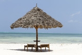 Isolated Wooden parasol and beach chairs in Zanzibar