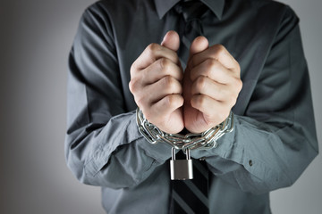 Businessman with chained hand