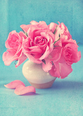 fresh pink roses in a ceramic vase on a blue background