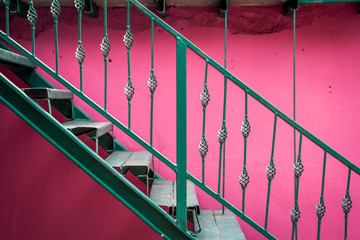 Metal staircase with pink wall