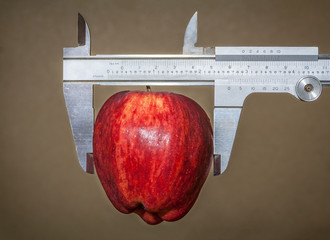Conceptual image of calipers and apple