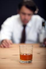 Alkoholiker schaut auf Glas, hält Flasche in Hand