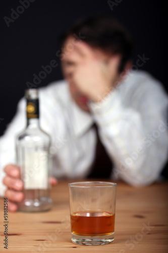 Alkoholtrinkender Mann mit Flasche  am Tisch - 59882586