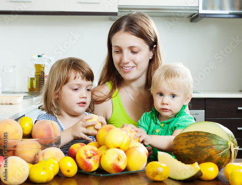 Ordinary woman with  daughters eating fruits