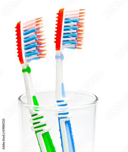 two toothbrushes in a glass beaker