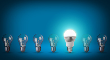 Idea concept on blue background. Row with light bulbs and LED bu