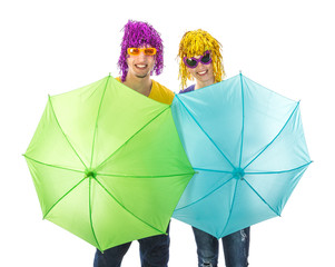 Trendy couple with sunglasses and wigs and umbrellas