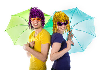 Trendy couple with sunglasses, wigs and umbrellas