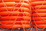 Stacked orange rescue round buoy, sea marine lifesaver