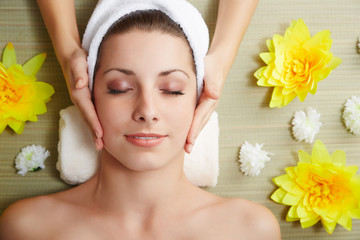 Beautiful young woman lying relaxed in a spa salon