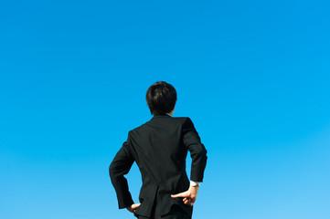 やる気を出す男性ビジネスマンの後ろ姿と青空