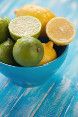 Glass bowl full of lemons and limes over wooden background