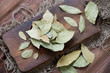 Dried bay leaves on a rustic cutting board, high angle view