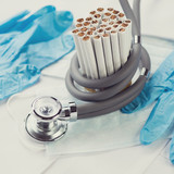 Bunch of cigarettes rounded by a stethoscope, close-up
