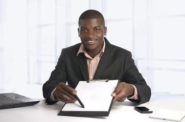 Afrikanischer Geschäftsmann zeigt auf Vertrag Textfreiraum