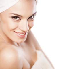 smiling beautiful girl with a towel on her head posing on white