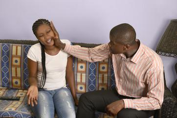 Junger afrikanischer Mann schlägt seine Freundin