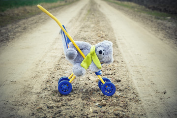 Children's strollers with toy bear abandoned on the road